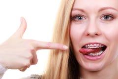 Mujer feliz que muestra sus apoyos en los dientes Imagenes de archivo