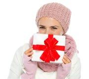 Mujer feliz que oculta detrás del rectángulo del regalo de Navidad Imagen de archivo