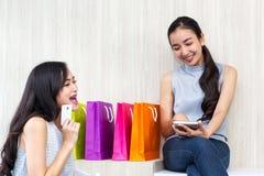 Mujer feliz que paga en café por la tarjeta de crédito y el teléfono elegante Mujer imagen de archivo libre de regalías