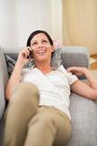 Mujer feliz que pone en el diván y el móvil de discurso Imagen de archivo libre de regalías