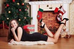 Mujer feliz que pone en el piso en Front Of Christmas Tree imagenes de archivo