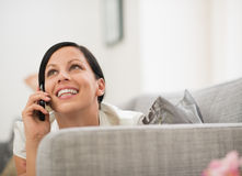 Mujer feliz que pone en el sofá y el móvil de discurso Fotos de archivo