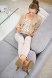 Mujer feliz que pone en el sofá y que usa la PC de la tableta Fotografía de archivo libre de regalías