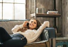 Mujer feliz que pone en el sofá y el teléfono celular que habla Imágenes de archivo libres de regalías