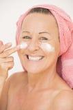 Mujer feliz que pone la crema en cara Foto de archivo libre de regalías