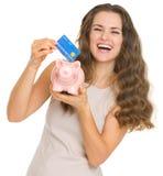 Mujer feliz que pone la tarjeta de crédito en la hucha fotografía de archivo
