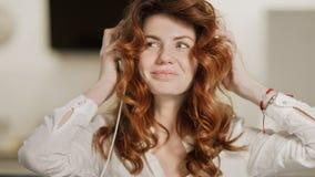 Mujer feliz que pone los auriculares en la cabeza en la sala de estar metrajes