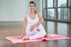 Mujer feliz que practica en la estera de la yoga fotografía de archivo