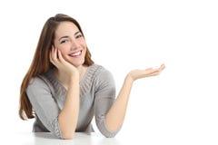 Mujer feliz que presenta con la mano abierta que lleva a cabo algo en blanco Imagenes de archivo
