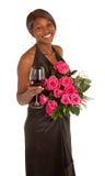 Mujer feliz que presenta con rosas y un vidrio de vino Foto de archivo libre de regalías