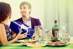 Mujer feliz que presenta el regalo al hombre en la tabla imágenes de archivo libres de regalías