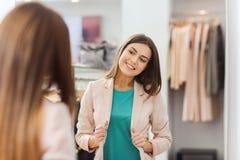 Mujer feliz que presenta en el espejo en tienda de ropa Imagen de archivo