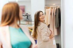 Mujer feliz que presenta en el espejo en tienda de ropa Imagen de archivo libre de regalías
