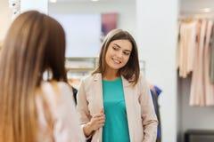 Mujer feliz que presenta en el espejo en tienda de ropa Imágenes de archivo libres de regalías