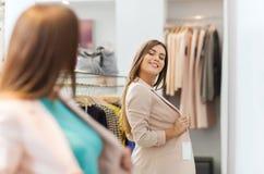Mujer feliz que presenta en el espejo en tienda de ropa Imagenes de archivo