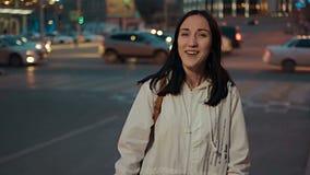 Mujer feliz que presenta en la calle delante de los semáforos borrosos de ciudad en la noche, color retro entonado metrajes