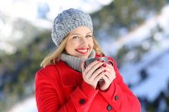 Mujer feliz que presenta en la montaña en invierno Fotos de archivo