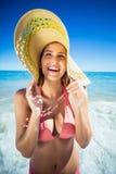 Mujer feliz que presenta en la playa Foto de archivo