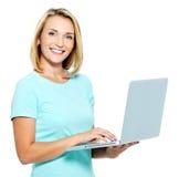 Mujer feliz que pulsa en la computadora portátil Fotografía de archivo