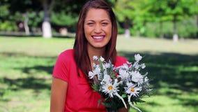 Mujer feliz que ríe mientras que se sostiene florece almacen de metraje de vídeo