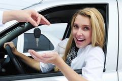 Mujer feliz que recibe clave del coche imagen de archivo libre de regalías