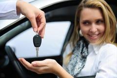 Mujer feliz que recibe clave del coche Imagen de archivo