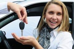 Mujer feliz que recibe clave del coche foto de archivo