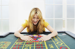 Mujer feliz que recoge a Chips At Roulette Table imagenes de archivo