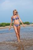 Mujer feliz que recorre en el agua Imagen de archivo libre de regalías