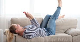 Mujer feliz que relaja y que toma el selfie usando cámara del teléfono móvil almacen de video