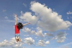 Mujer feliz que salta al cielo azul del clound Fotos de archivo