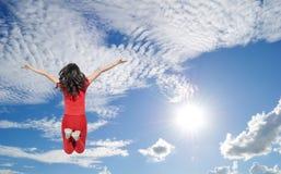 Mujer feliz que salta al cielo azul del clound Imagenes de archivo