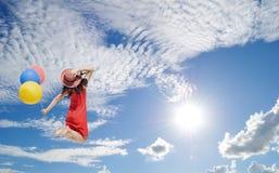 Mujer feliz que salta al cielo azul del clound Foto de archivo