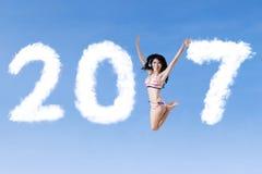 Mujer feliz que salta con 2017 Imagenes de archivo