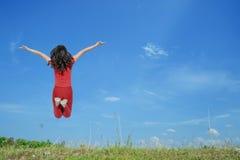 Mujer feliz que salta con el cielo azul al aire libre Foto de archivo