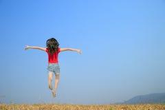 Mujer feliz que salta con el cielo azul al aire libre Imágenes de archivo libres de regalías
