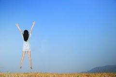 Mujer feliz que salta con el cielo azul al aire libre Fotos de archivo
