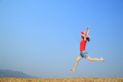 Mujer feliz que salta con el cielo azul al aire libre en día relajante Foto de archivo libre de regalías