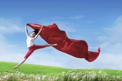 Mujer feliz que salta con la bufanda roja Foto de archivo