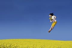 Mujer feliz que salta con la flor foto de archivo