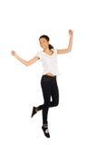 Mujer feliz que salta con las manos para arriba Fotografía de archivo