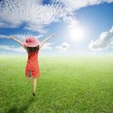 Mujer feliz que salta en campos de hierba verde con el cielo de las nubes Fotografía de archivo
