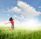 Mujer feliz que salta en campos de hierba verde con el cielo de las nubes Imagenes de archivo