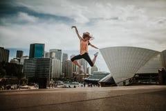 Mujer feliz que salta en el aire en Sydney imagenes de archivo