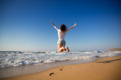 Mujer feliz que salta en la playa Imagenes de archivo