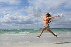 Mujer feliz que salta en la playa el días de fiesta Imágenes de archivo libres de regalías