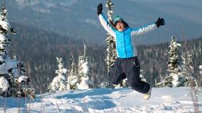 Mujer feliz que salta en las montañas del invierno, naturaleza de goce femenina activa, Fotografía de archivo