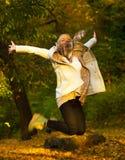 Mujer feliz que salta en un día del otoño Imagenes de archivo