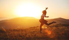 Mujer feliz que salta y que disfruta de vida en la puesta del sol en montañas Foto de archivo