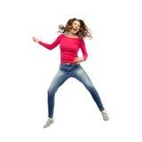 Mujer feliz que salta y que finge jugar de la guitarra Fotos de archivo